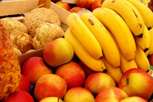 Apples, tubers, banannas and a pineapple at the market