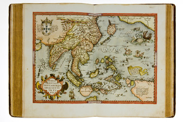 Open ancient atlas with map of South East Asia