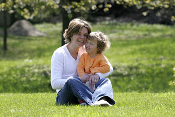 mother and girl sitting on the grass