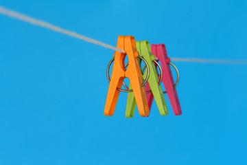 Three washing pegs hanging on a washing line.