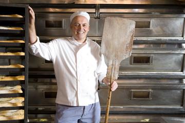 Baker in bakery, smiling, portrait