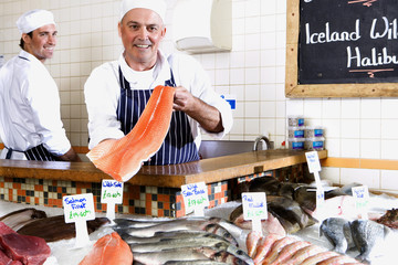 Fishmonger behind counter holding up fillet of fish, smiling, portrait