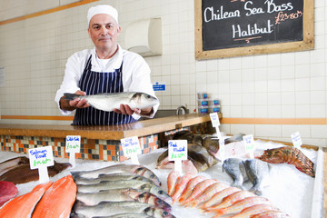 Fishmonger behind counter in shop, holding out fish, portrait