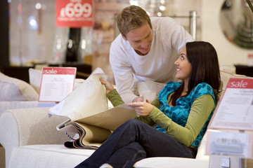 Young couple with fabic samples in shop, smiling at each other