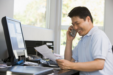 Man in home office on telephone smiling