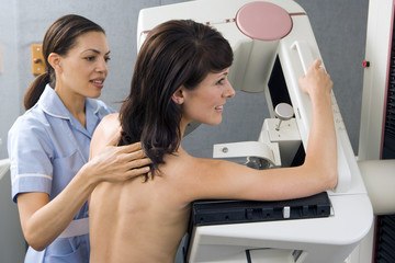 Patient having breast scan in hospital, nurse assisting, side view