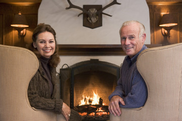 Couple sitting by fireplace smiling