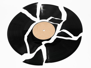 Broken vinyl record against a white background