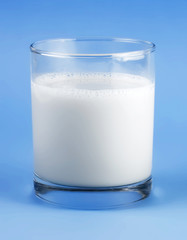 Glass of milk isolated on blue background
