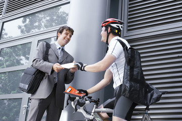 Bicycle courier delivering package to businessman, smiling, side view, low angle view