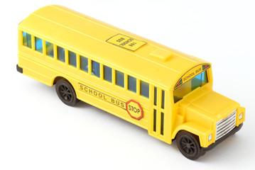 plastic yellow toy school bus on white background