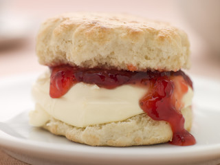 Scone Filled with Strawberry Jam and Clotted Cream on a plate