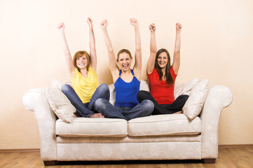 three girls sitting on a lounge are cheering