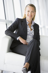 Businesswoman sitting in office lobby smiling