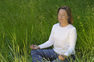 Woman Meditating in Field of Grass