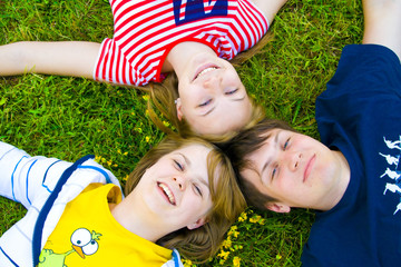Three friends lay on a grass