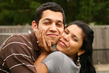 Happy hispanic couple hugging