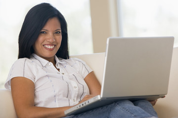 Woman in living room using laptop smiling