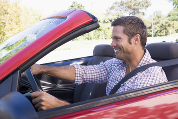 Man driving convertible car smiling