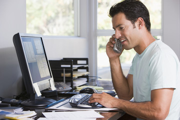 Man in home office on telephone using computer and smiling