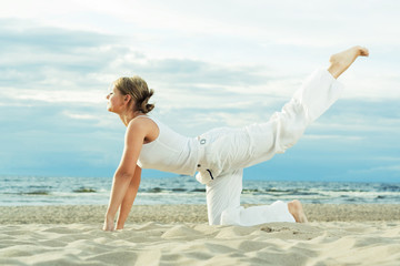 Young cute girl training on the beach.