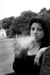 Woman smoking a cigarette looking stressed.