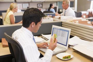 Businessman in cubicle eating sandwich