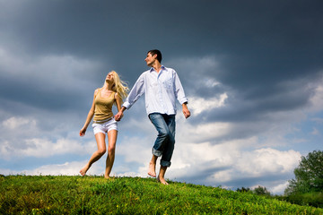 Young couple walking through summer lawn Wall mural