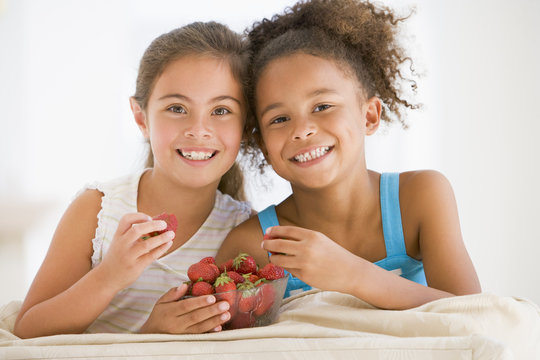 Two young girls eating strawberries in living room smiling