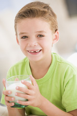 Young boy indoors drinking milk smiling
