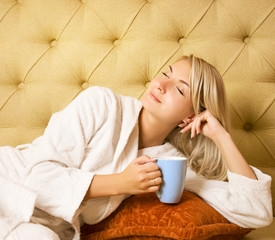 Bautiful young woman sitting on a bed and drinking cofee