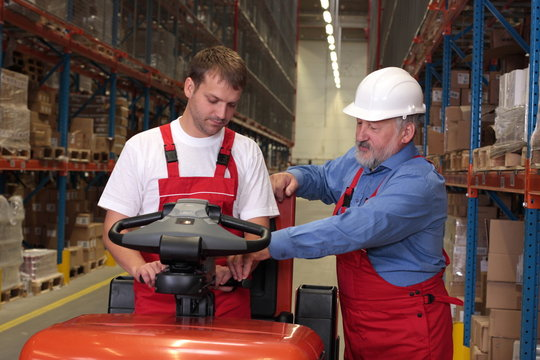 A senior worker teaching  junior the operation of a fork lift