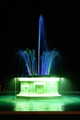 Colored fountain at night lit blue-green