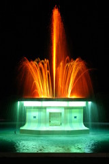Colored fountain at night lit orange-green