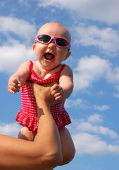 Happy Baby girl in swimsuit under clouds