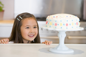 Young girl at kitchen counter looking at cake smiling