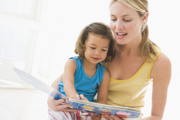 Mother and daughter indoors reading book and smiling