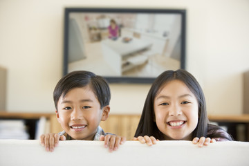 Two young children in living room with flat screen television sm