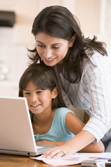 Woman and young girl in kitchen with laptop and paperwork