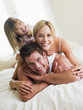 Family in bed playing and smiling