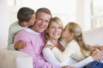 Family sitting in living room kissing and smiling
