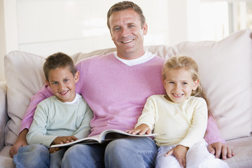 Man and two children sitting in living room reading book and smi