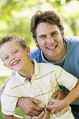 Man and young boy outdoors embracing and smiling