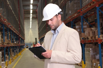 worker making notes at the warehouse