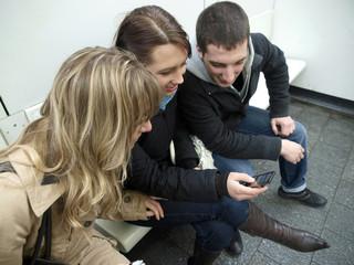 Jugendliche schauen sich einen Videoclip auf dem Handy an.