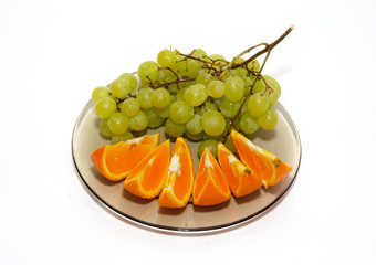 Green grapes and orange isolated on white.