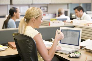 Businesswoman in cubicle using laptop eating sushi