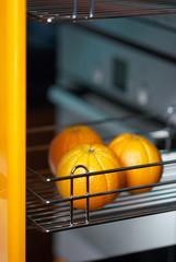 Tasty orange in kitchen in fridge