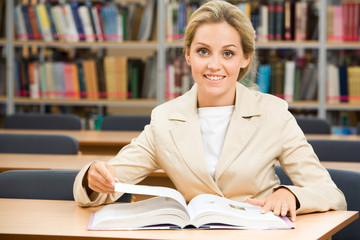 Portrait of happy student sitting in library before textbook