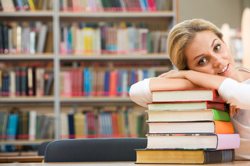 Portrait of tired student lying on the stack of books